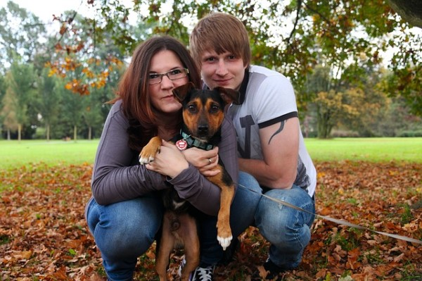 couple posing with new rescue dog