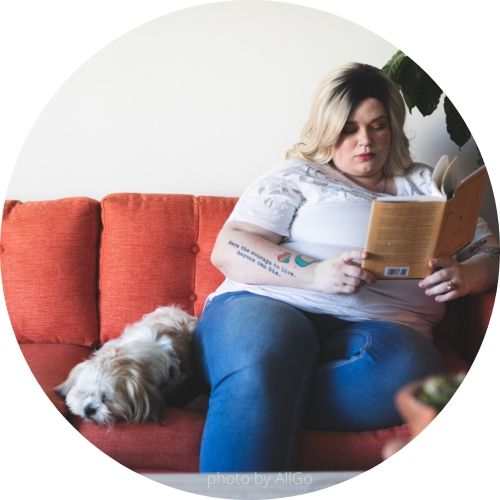 woman reading book on couch with dog as a good example of how to help a rescue dog adjust
